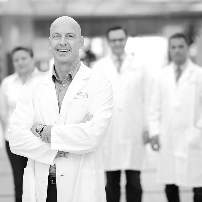 Praxisfotografie mit Ärzten in der Klinik, Gruppenfoto in Schwarzweiss, Gruppenaufnahme von Stefan Obermeier Fotografie, Teamfoto mit unscharfem Hintergrund